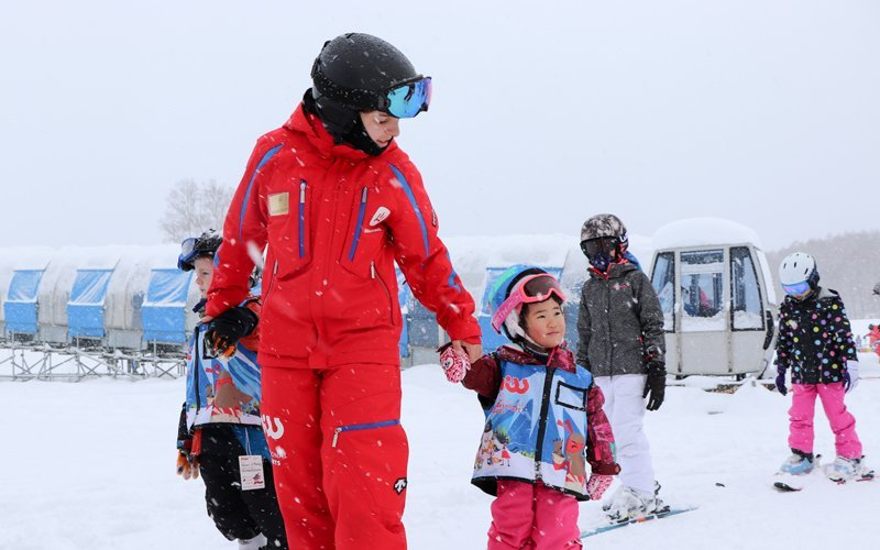 NISSのスキーインストラクターに手を引かれて歩く子供